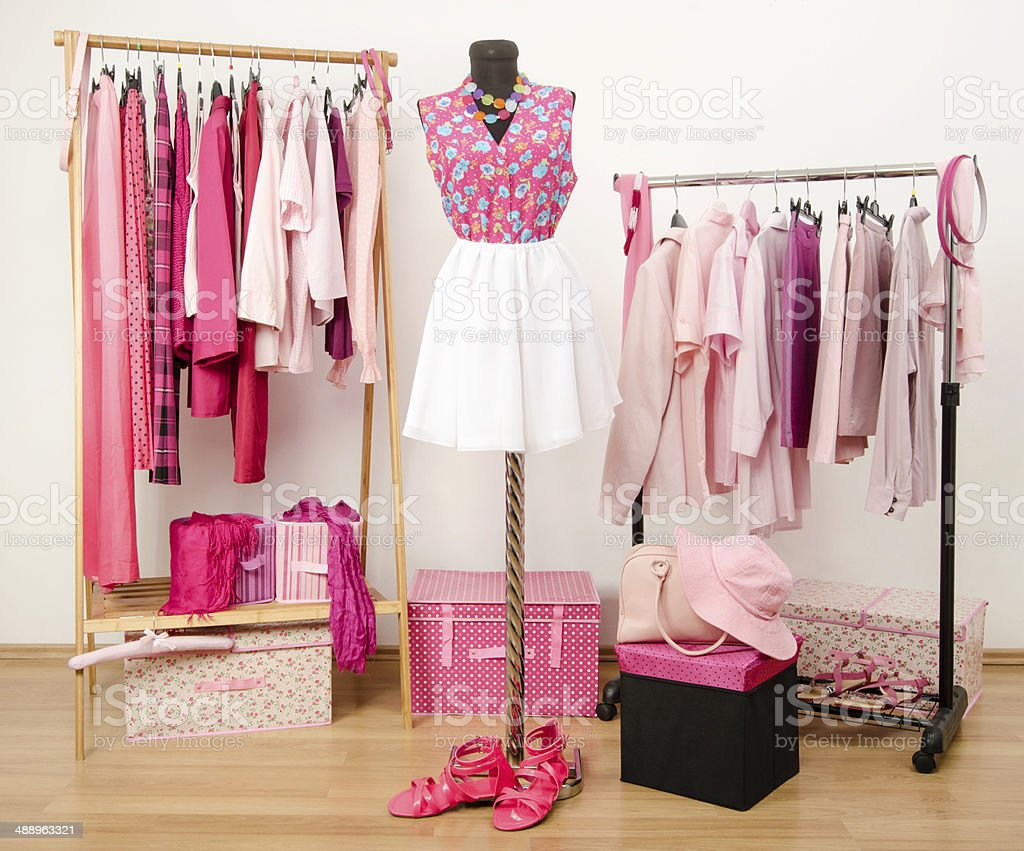 Wardrobe with all shades of pink clothes, shoes and accessories. stock photo
