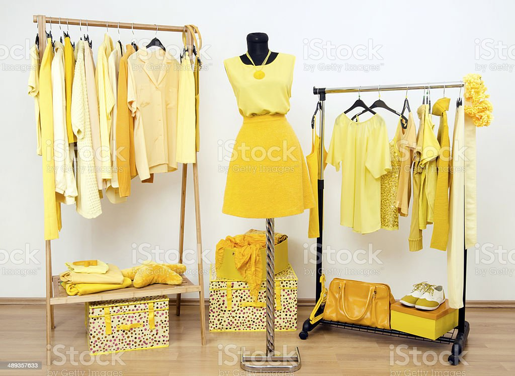 Wardrobe with all shades of yellow clothes, shoes and accessories. stock photo