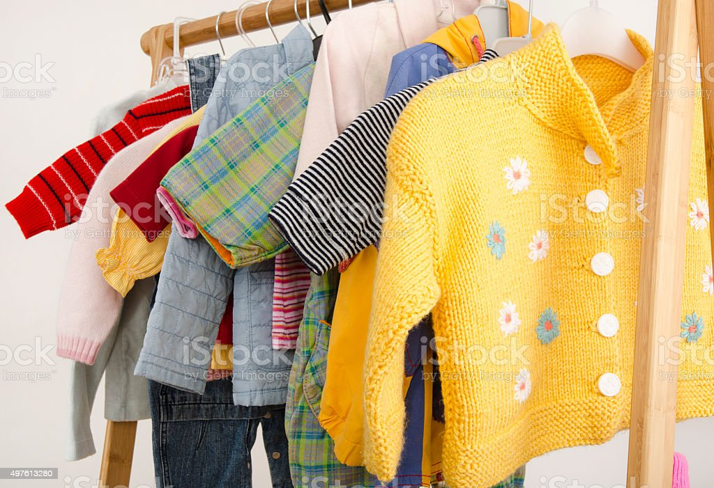 Wardrobe with baby clothes arranged on hangers. stock photo