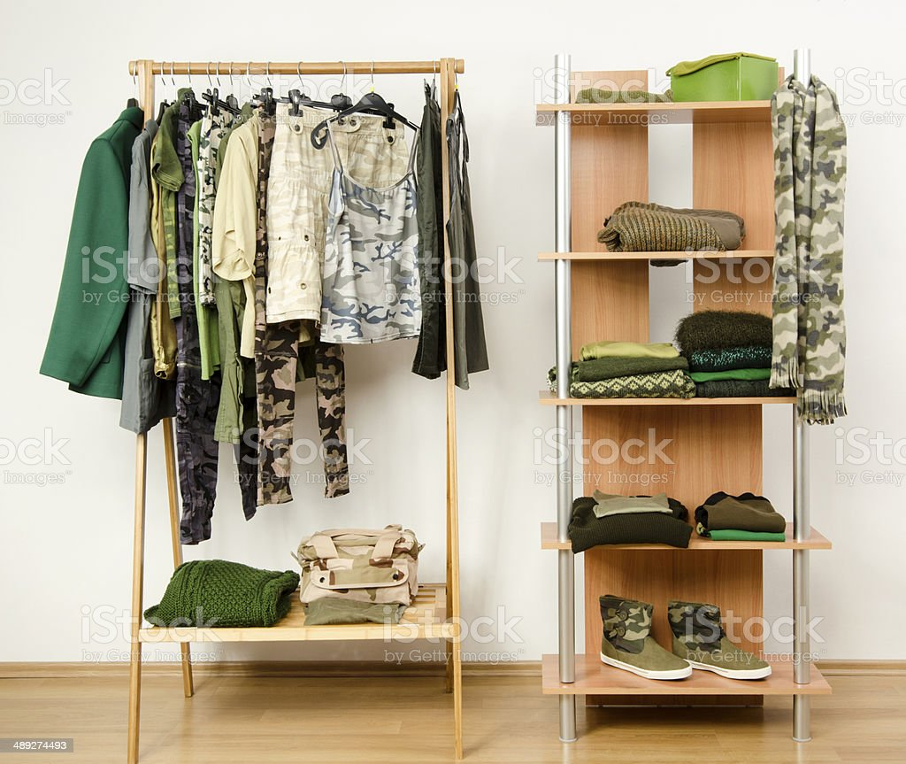 Wardrobe with camo pattern clothes, shoes and accessories. stock photo