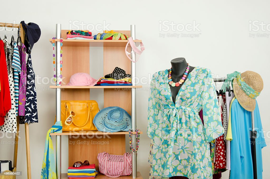Wardrobe with clothes and a beach outfit on a mannequin. stock photo