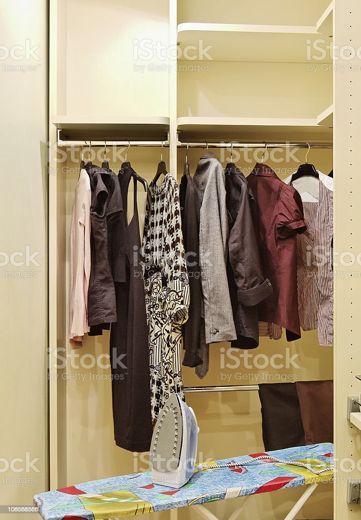 Wardrobe with clothes and ironing board stock photo