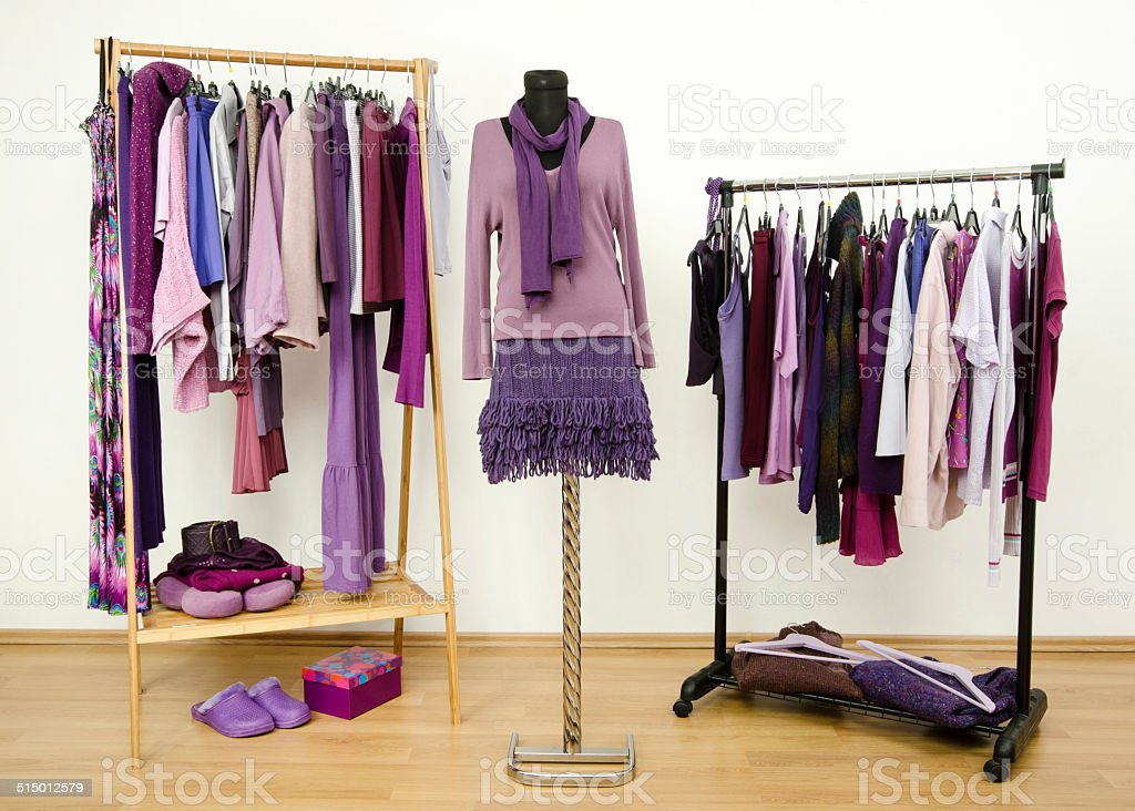 Wardrobe with purple clothes on hangers, an outfit on mannequin. stock photo
