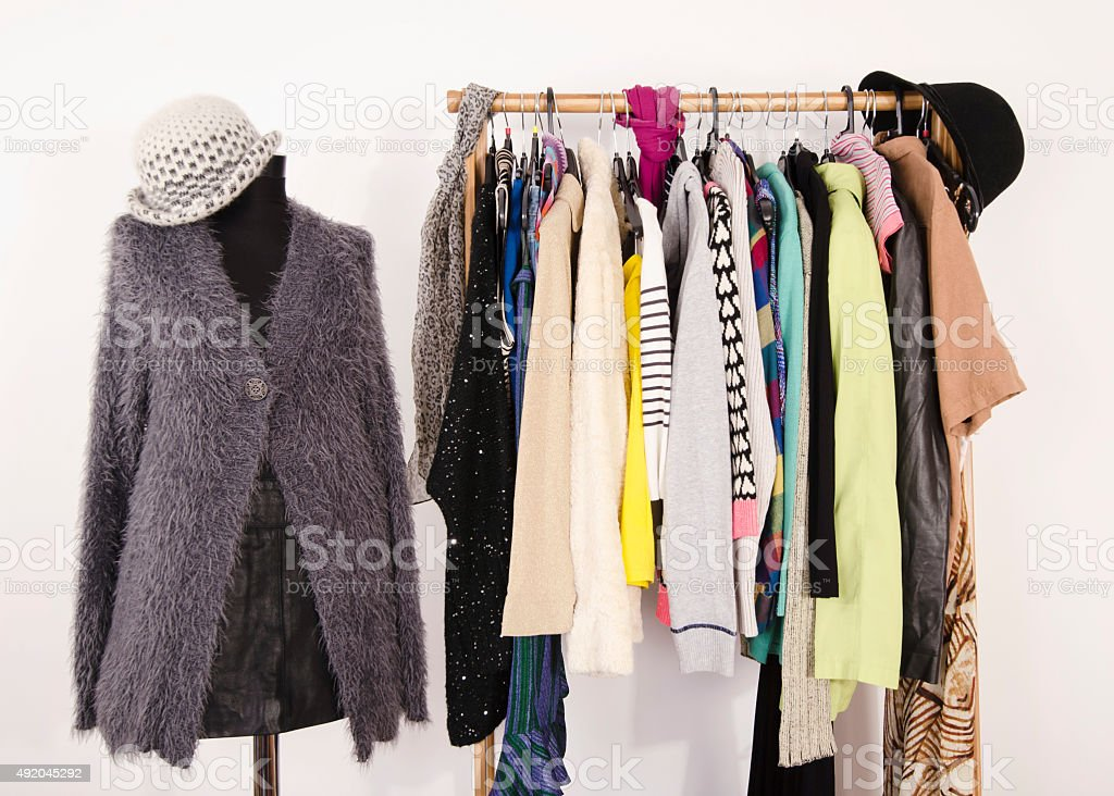Wardrobe with winter clothes arranged on hangers. stock photo