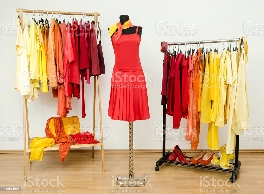 Wardrobe with yellow, orange, red clothes and dress on mannequin. stock photo