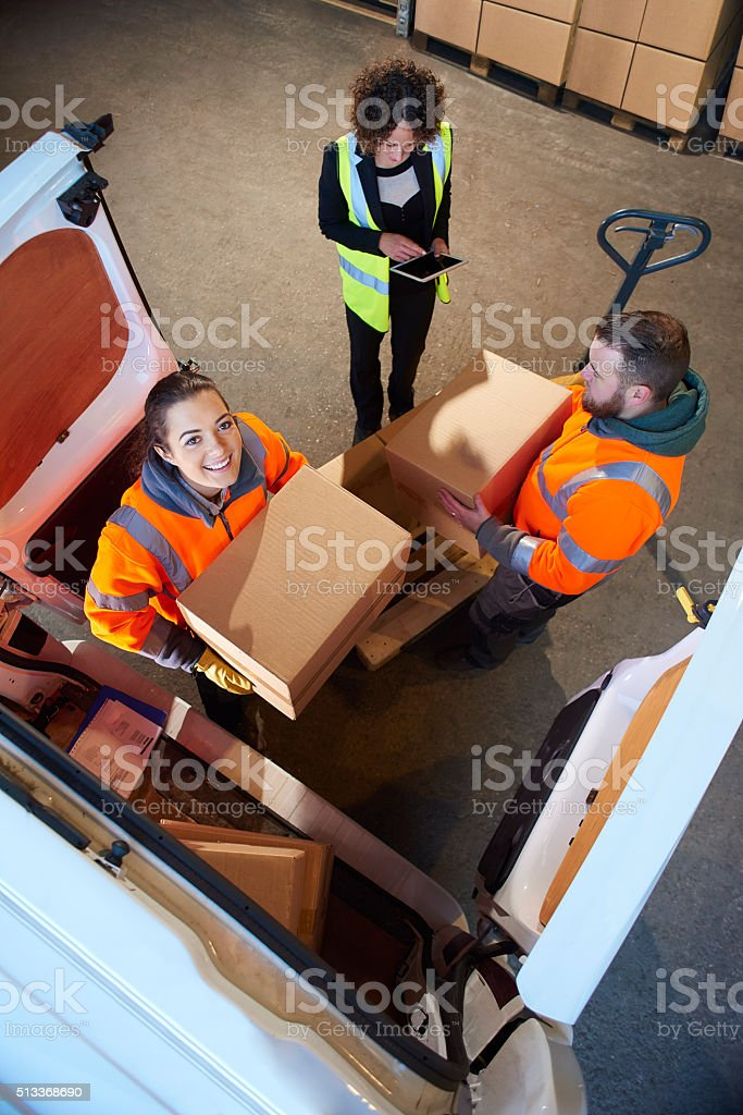warehosue workers loading a courier's van . stock photo