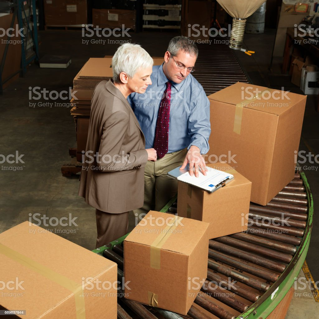 Warehouse Businesspeople Reviewing Documents stock photo