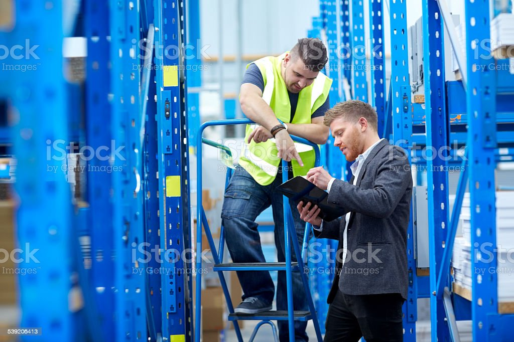 Warehouse employees checking inventory stock photo