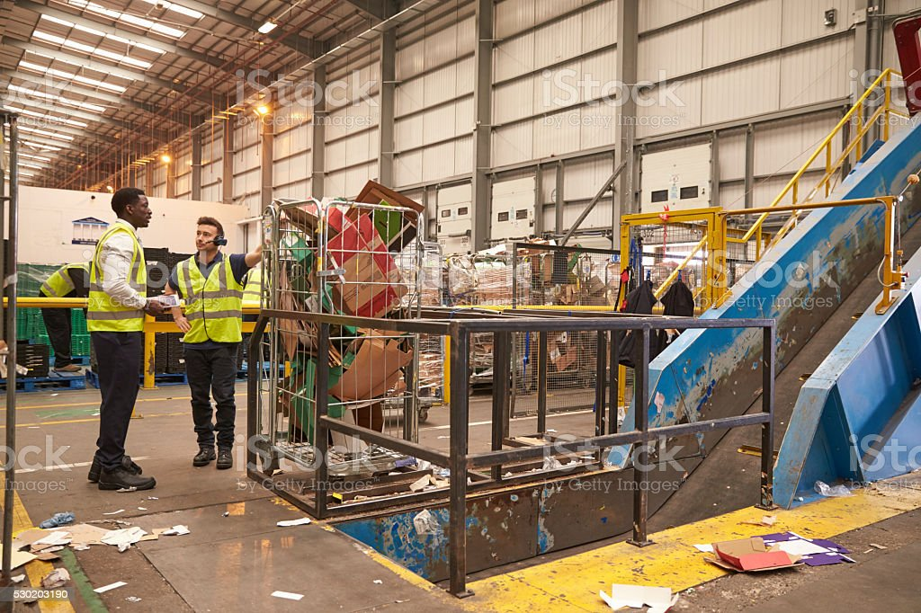 Warehouse manager and colleague talk by recycling machinery stock photo
