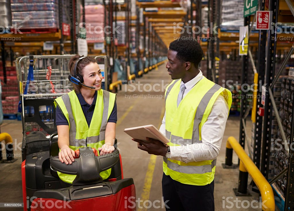 Warehouse manager and woman on tow tractor in discussion stock photo