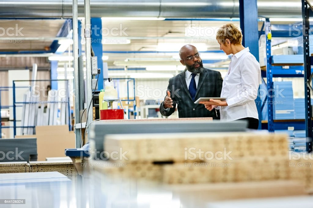 Warehouse manager discussing work with  supervisor stock photo
