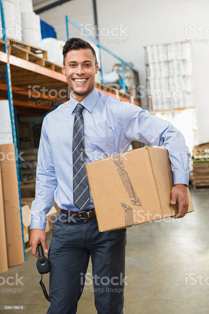 Warehouse manager holding cardboard box and scanner stock photo