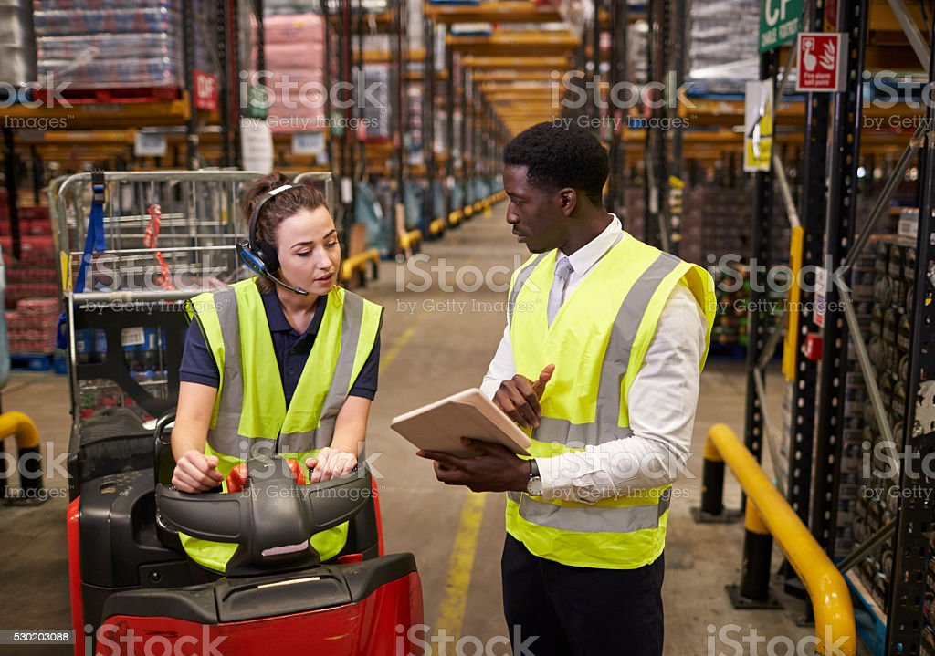 Warehouse manager instructing woman operating tow tractor stock photo