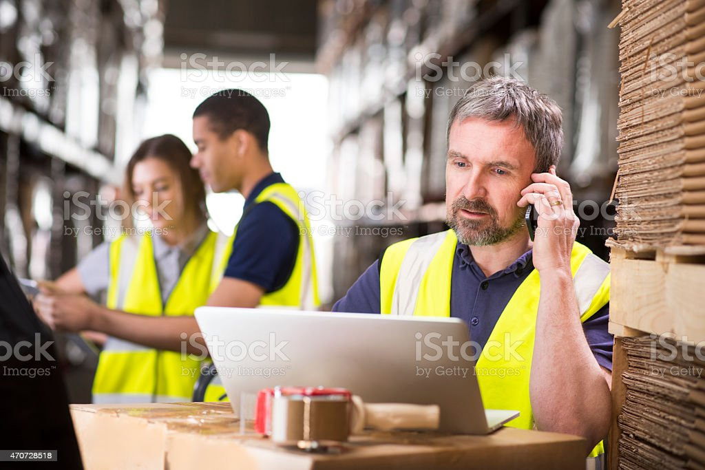 warehouse manager ringing a customer stock photo