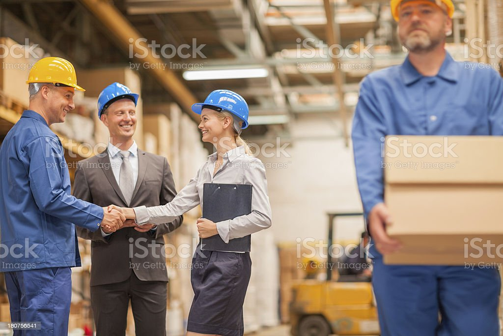 Warehouse manager shaking hands with worker royalty-free stock photo