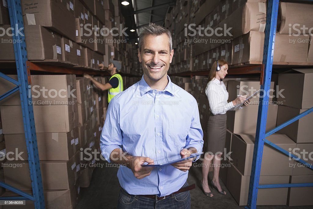Warehouse manager smiling at camera stock photo