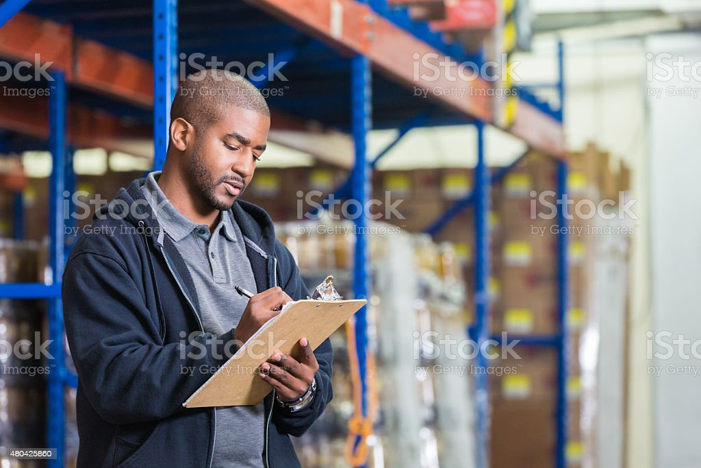Warehouse manager taking inventory in food bank pantry stock photo