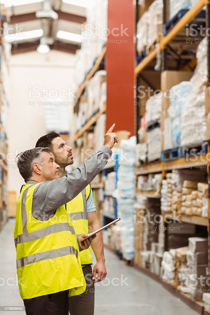 Warehouse manager talking with worker stock photo