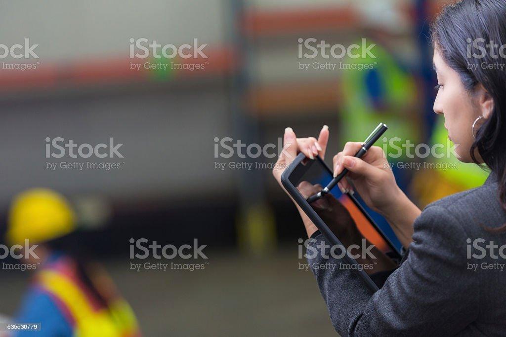 Warehouse supervisor checking distribution order on digital tablet stock photo