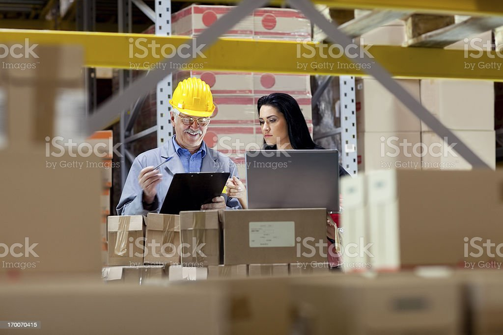 Warehouse worker and Iinspector, controller,  checking inventory royalty-free stock photo