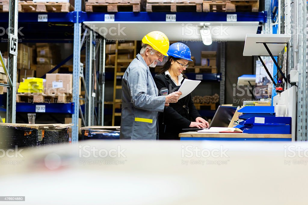 Warehouse worker and Iinspector, controller,  checking inventory stock photo