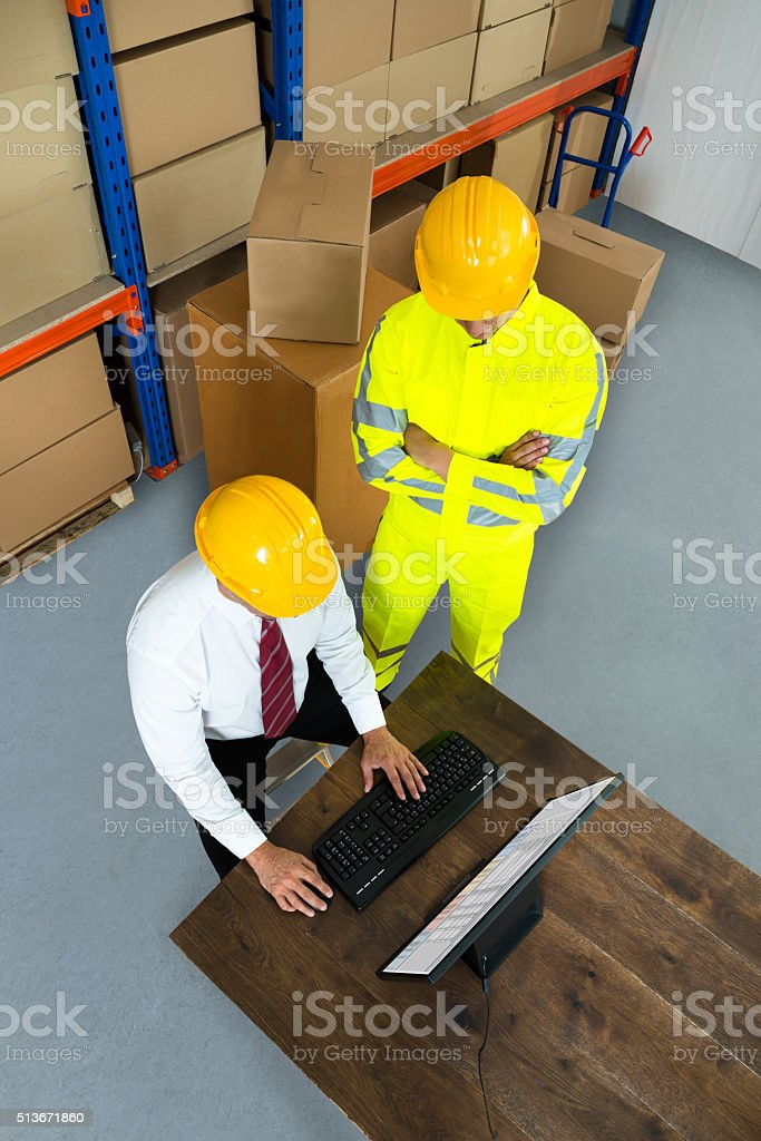 Warehouse Worker And Manager Using Computer stock photo