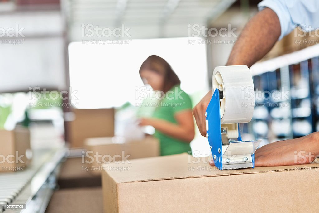 Warehouse worker assembling packages in assembly line stock photo