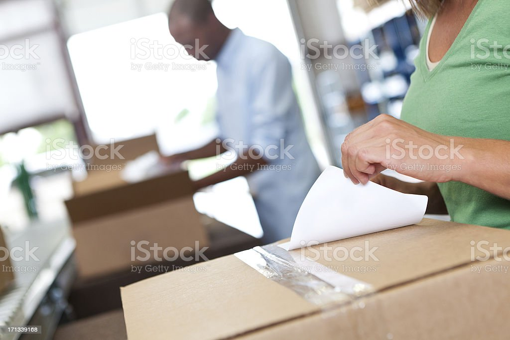 Warehouse worker attaching label onto box being shipped royalty-free stock photo
