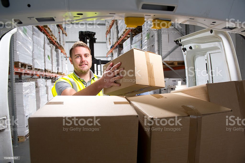 Warehouse Worker Loading a Delivery Van stock photo