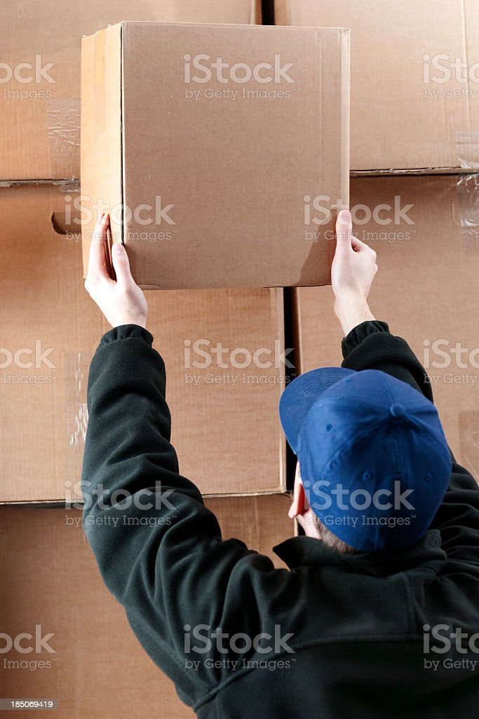 One worker is standing a large warehouse. He moves a cardboard box...
