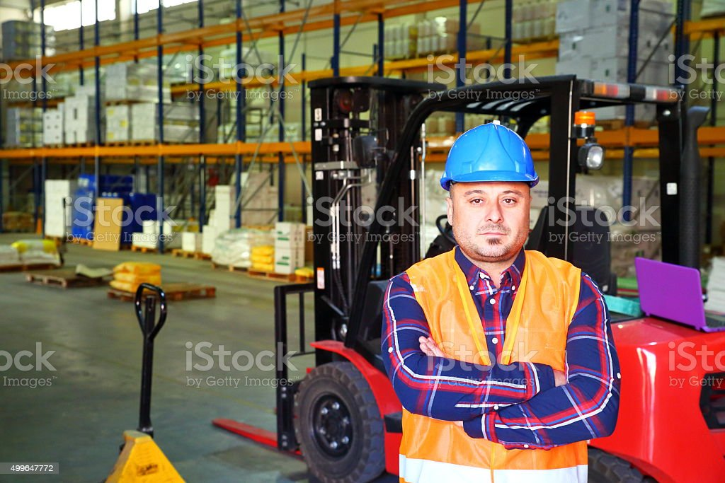 Warehouse worker operating forklift stock photo