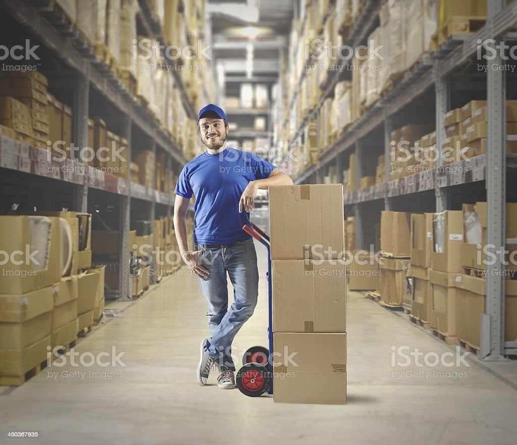 Warehouse worker posing for a photo with a stack of boxes stock photo