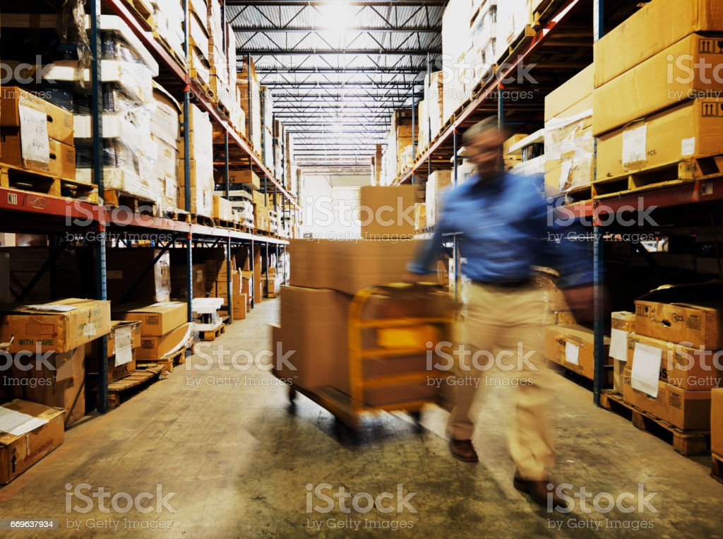 Warehouse Worker Pulling Boxes stock photo