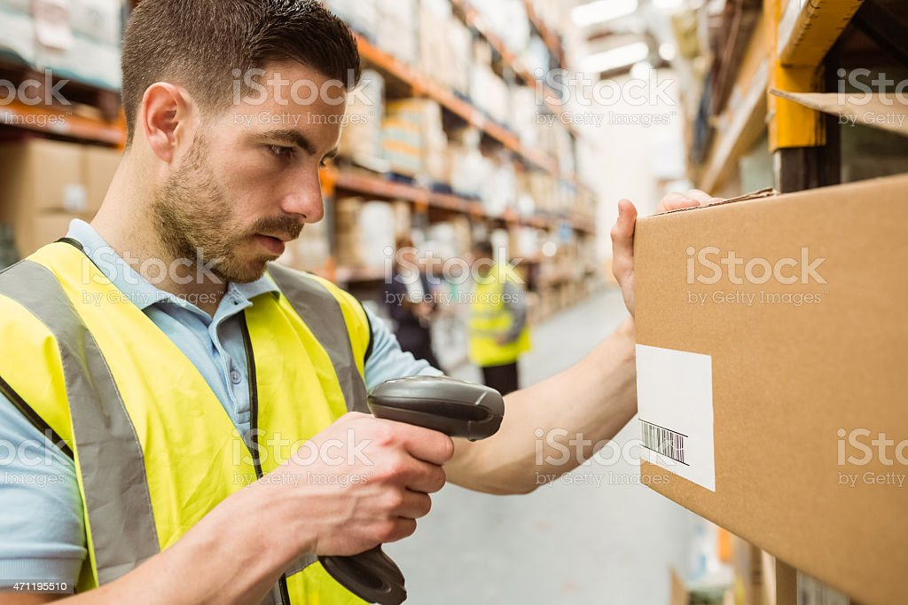 Warehouse worker scanning barcodes on boxes stock photo