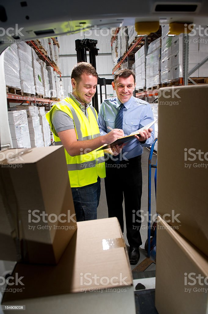 Warehouse Worker Signing Off on a Delivery royalty-free stock photo