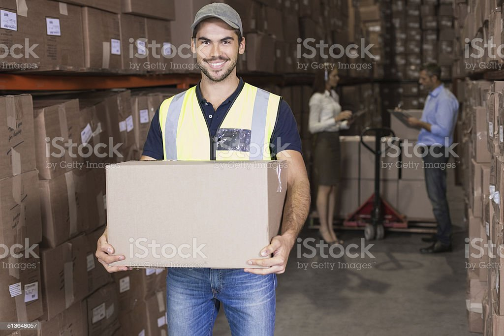 Warehouse worker smiling at camera carrying a box stock photo