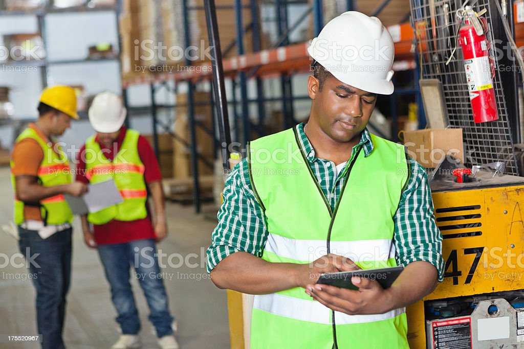 Warehouse worker using digital tablet to inventory products royalty-free stock photo