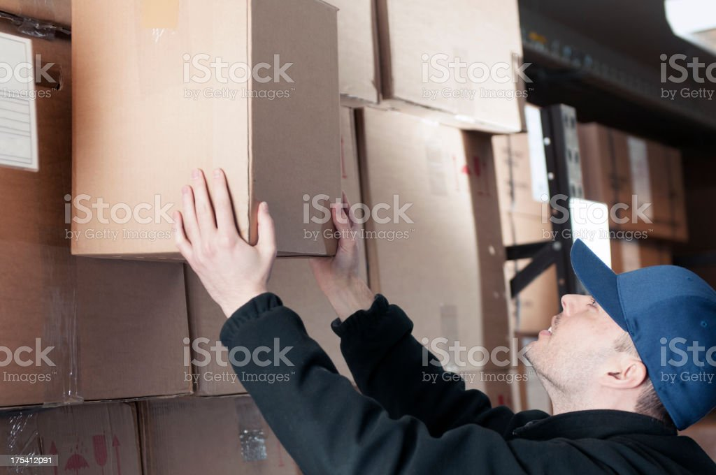 Warehouse worker with blue hat moving a cardboard box  stock photo