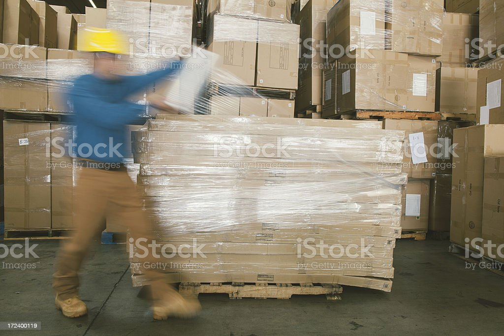 warehouse worker wrapping boxes royalty-free stock photo