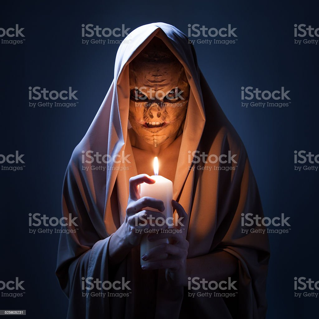 Warlock with candle in darkness. stock photo