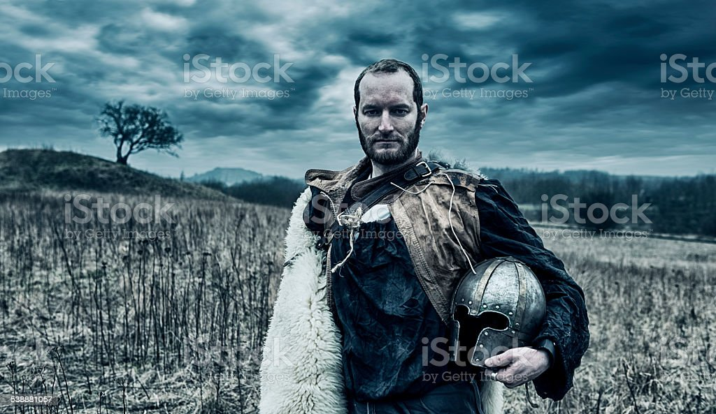 Warlord stands on the battlefield holding helmet stock photo
