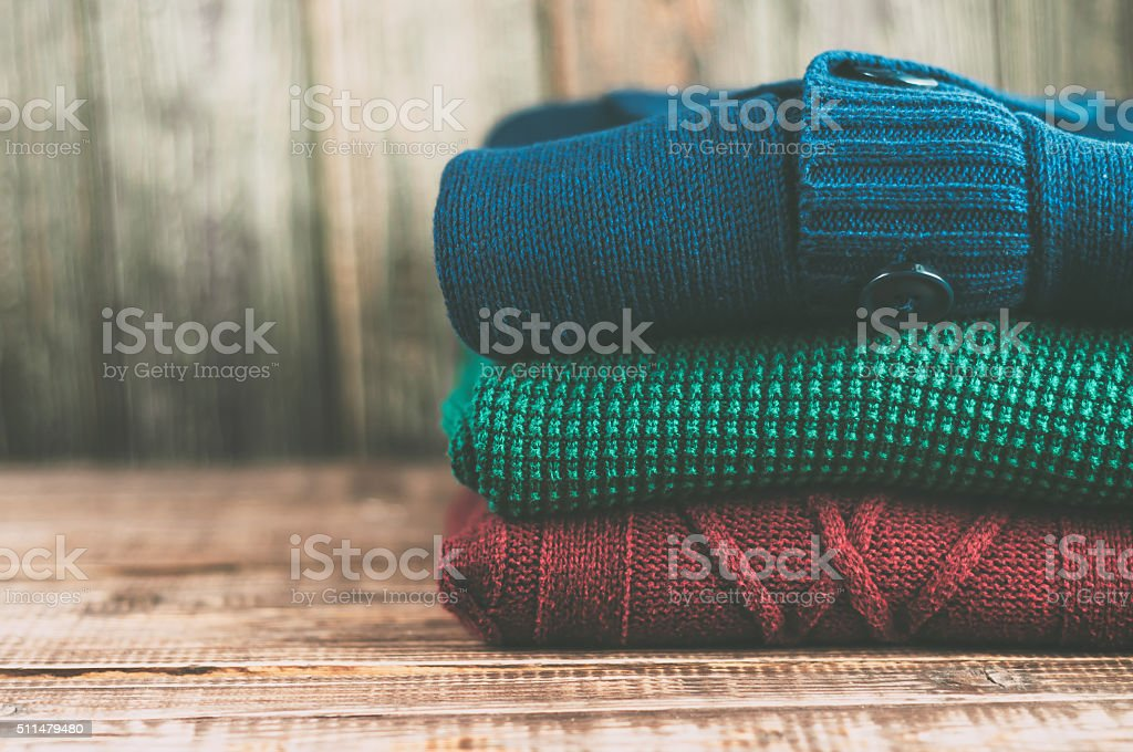 Warm clothes laid in a pile on wooden background. stock photo