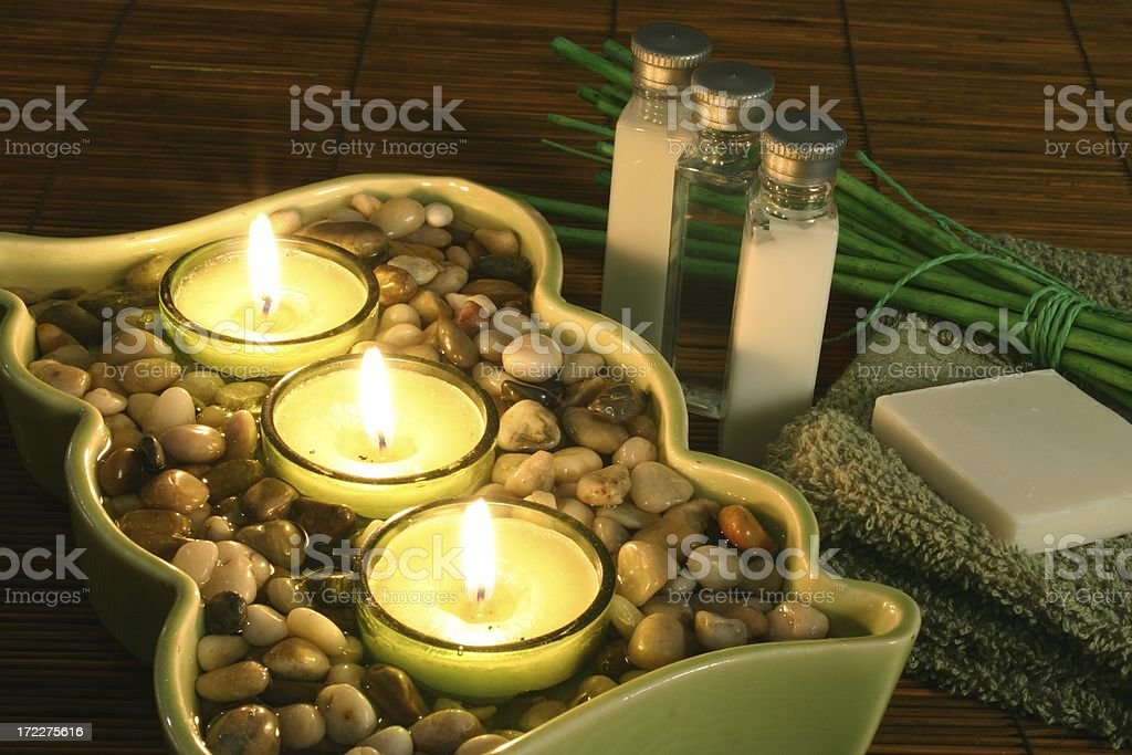 Warm Glow spa set up with candles and rocks royalty-free stock photo