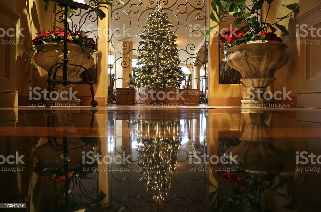 Warm holiday reflection of christmas tree in marble floor stock photo