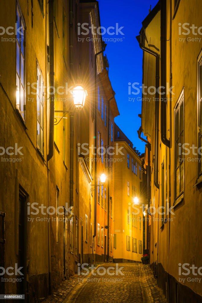 Warm lamplight illuminating picturesque cobbled street Gamla Stan Stockholm Sweden stock photo
