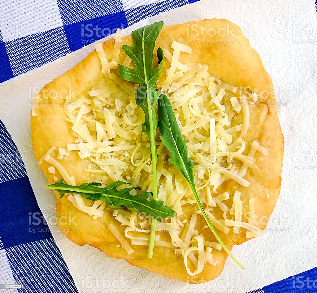 Warm langos with cheese, garlic cream and arugula stock photo