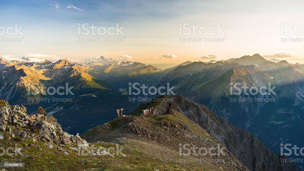 Warm light at sunrise on mountain peaks, ridges and valleys stock photo