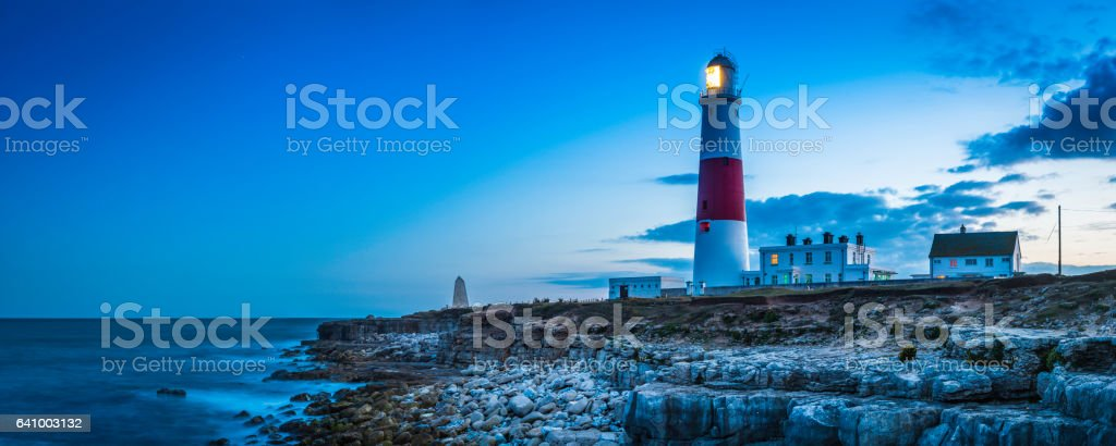 Warm light of lighthouse glowing over rocky ocean shore panorama stock photo