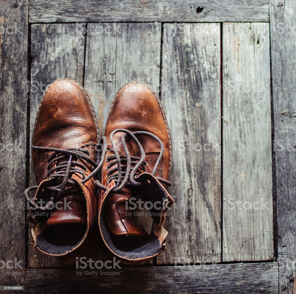 Warm men's leather boots on rustic brown wooden  background stock photo