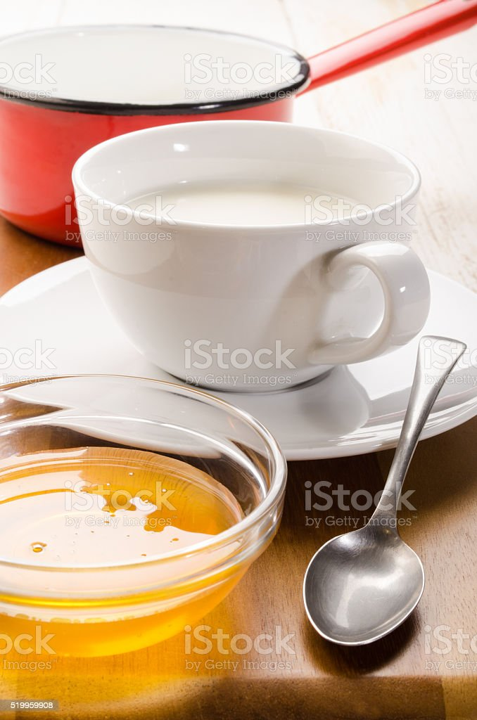 warm milk in a cup and acacia honey stock photo
